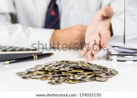 Pile of coins with hand that  gesture something as money savings, investment or any financial concept - stock photo