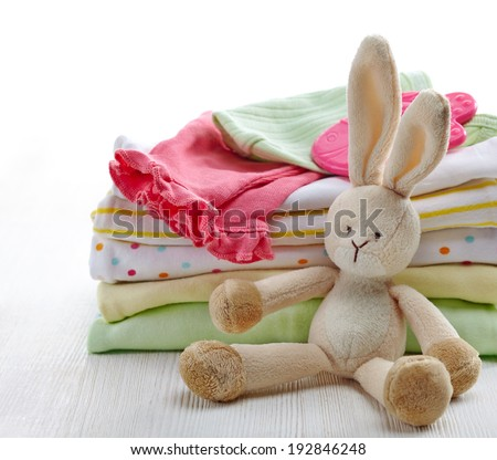 Pile of colorful baby clothes and toy on white wooden background - stock photo