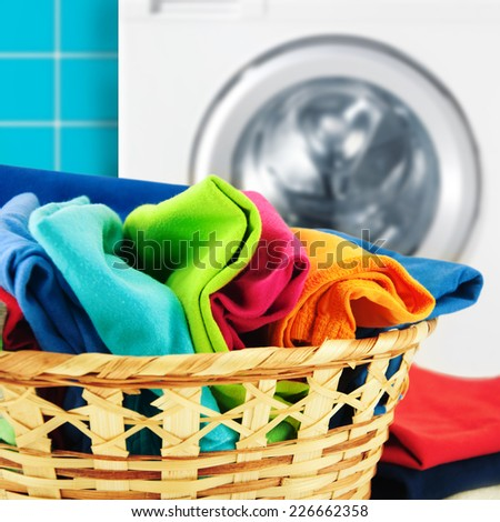 Pile of colorful clean clothes with washing machine. - stock photo