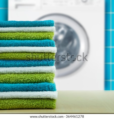 Pile of colorful clean towels with washing machine. - stock photo