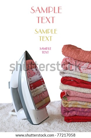 Pile of colorful clothes and electric iron - stock photo
