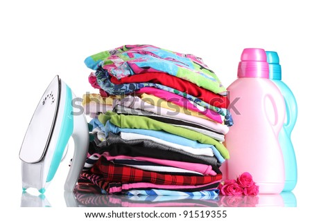 Pile of colorful clothes and electric iron with detergent isolated on white - stock photo