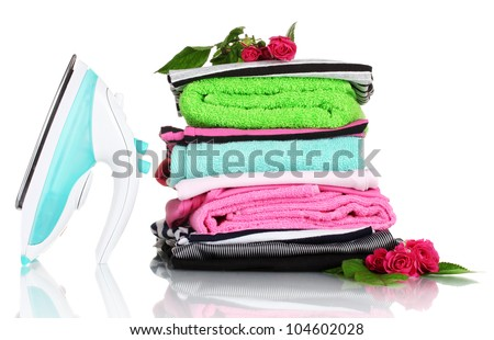 Pile of colorful clothes and electric iron with roses isolated on white