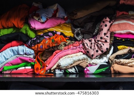 Pile of colorful clothes in a closet.