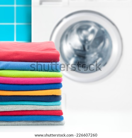 Pile of colorful clothes with washing machine. - stock photo