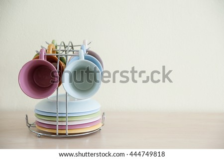 Pile of colorful coffee cups on wooden table with cream background.Right space frame.