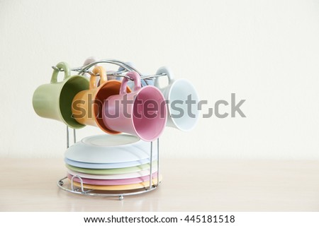Pile of colorful coffee cups on wooden table with cream background. Right space frame.