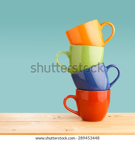 Pile of colorful cups on wooden table on blue background - stock photo