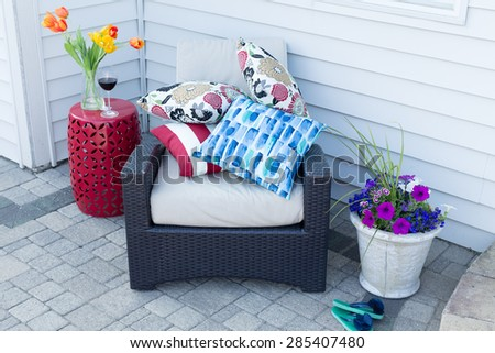 Pile of colorful cushions on a comfortable outdoor armchair flanked with fresh spring tulips and flowers for a relaxing place to enjoy a shady break on a hot day - stock photo