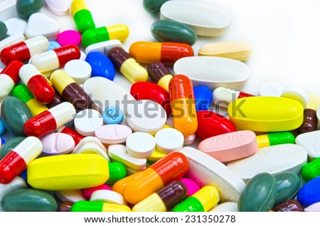 Pile of colorful drugs pills capsules and medical medicine for health care industry in white isolated background. Used for health or drugs addiction concept