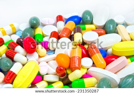Pile of colorful drugs pills capsules. And medical medicine for health care industry in white isolated background. Used for medical health or drugs addiction concept