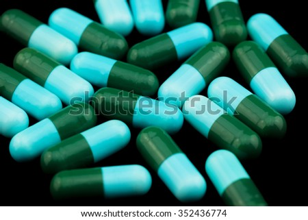 Pile of colorful drugs pills capsules for health care industry in black background - stock photo