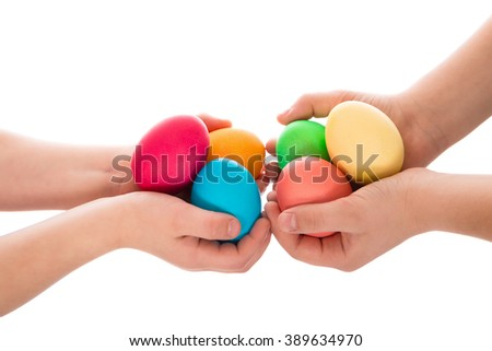 Pile of colorful easter eggs in two child hands after egg-hunt, isolated on white background - stock photo
