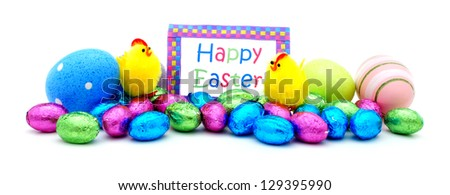 Pile of colorful eggs, candy and toys with Happy Easter card over white - stock photo