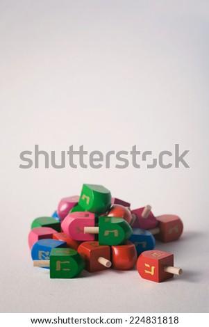 Pile Of Colorful Hanukkah Dreidels On White - stock photo