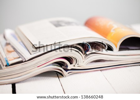 Pile of colorful magazines on a white table - stock photo