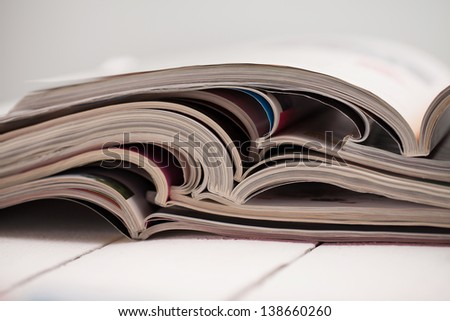 Pile of colorful magazines on a white table