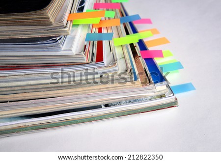 Pile of colorful magazines with bookmarks - stock photo