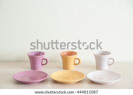 Pile of colorful modern coffee cups on wooden table with dishes for prepare serve.