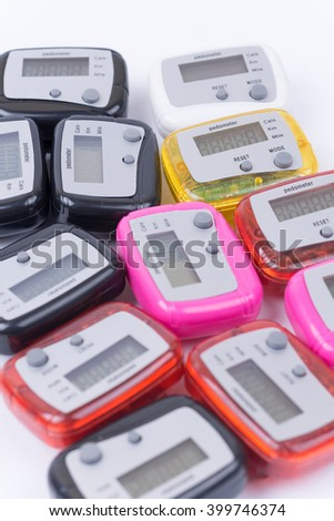 Pile of colorful pedometers over white background.