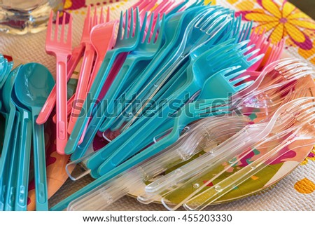 pile of colorful plastic cutlery for the birthday party