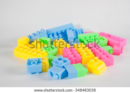 Pile of colorful plastic toy construction bricks isolated over the white as a  background. - stock photo