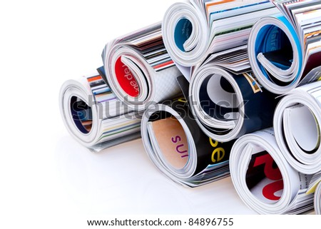Pile of colorful rolled magazines ; isolated on white background.