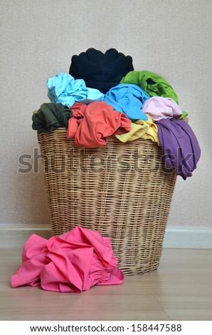 pile of colorful shirts in a wicker basket - stock photo