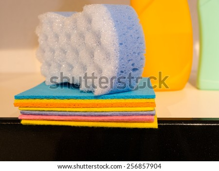 Pile of colorful soft absorbent cloths and sponge for cleaning the house stacked on a kitchen counter ready for use - stock photo