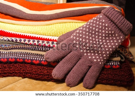 Pile of colorful warm winter Christmas clothes and a winter glove - stock photo