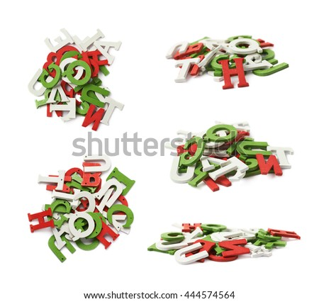 Pile of colorful white, red, green colored wooden letters isolated over the white background - stock photo