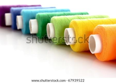 Pile of coloured bobbins of lurex thread isolated on white - stock photo