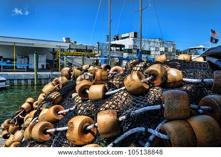 Pile of commercial fishing nets with floats in front of a Florida seafood processing plant - stock photo