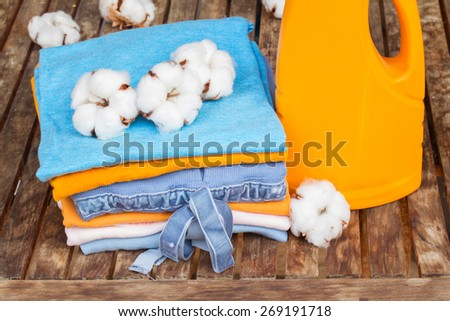 pile of cotton clothes with raw cotton buds and bottle of detergent on wooden table - stock photo