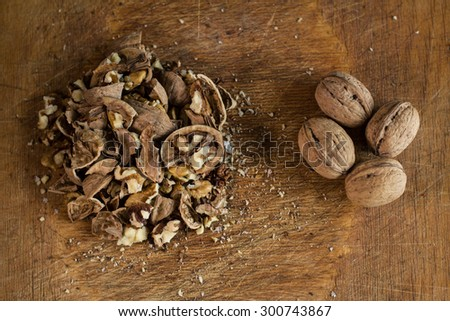 Pile of cracked walnuts close to four whole ones