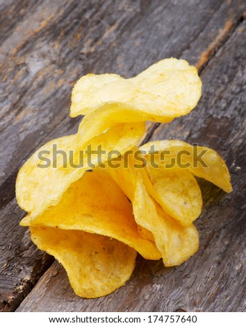 Pile of Crispy Cheese Potato Chips closeup on Rustic Wooden background - stock photo