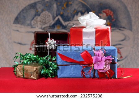 Pile of decorative gift boxes on red table on Christmas or New year blurred background - stock photo