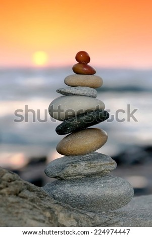 Pile of delicately balanced stones with the ocean and sunset in the background