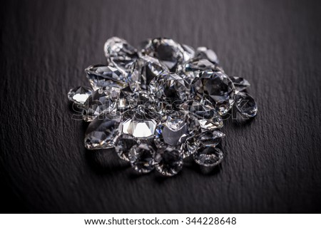 Pile of diamonds on dark metal surface - stock photo