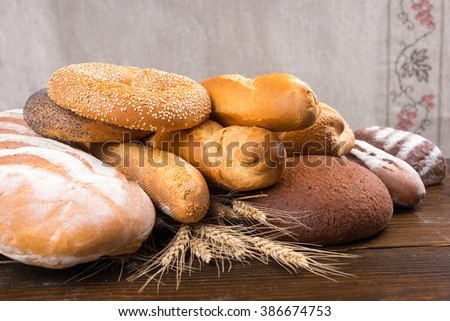Pile of different types of baked bread loaves, baguettes, bagels and rolls on top of whole wheat stalks over wood table