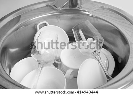 Pile of dishes in sink closeup - stock photo