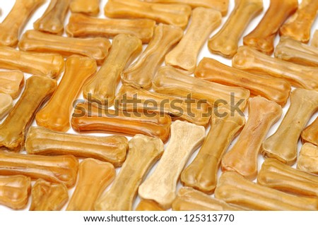 Pile of dog biscuits in the shape of a bone on a white great for a pet food background - stock photo
