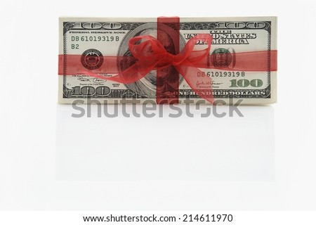 Pile of 100 dollar bills tied in a red bow conceptual of an award, gift, financial success, bonus or bribe, with copyspace below - stock photo