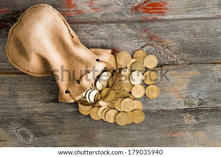 Pile of dollar coins spilling out of a drawstring pouch onto a rustic old weathered wooden table, view from above with copy space - stock photo