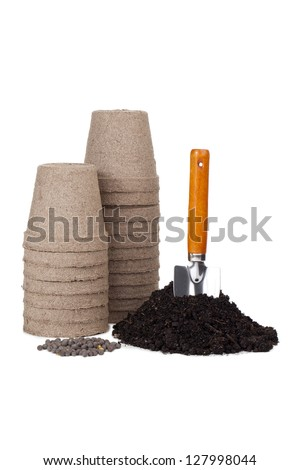 Pile of empty pots, nitrogen fertilizer, and organic soil with entrenched shovel