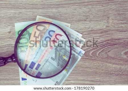 pile of euro banknotes money under looking glass - stock photo