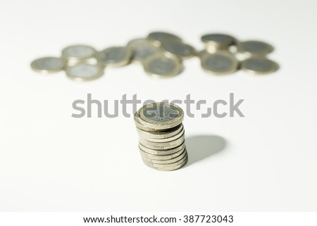 Pile of Euro coins with many more blurred in the background