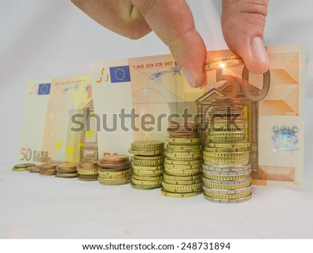 pile of euros money like graph, light beam, hand  putting coins - stock photo