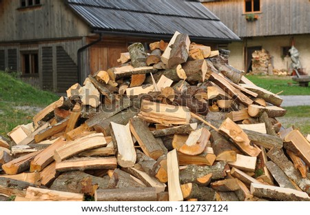 Pile of firewood and old houses - stock photo
