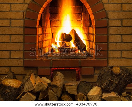 pile of firewood and tongues of fire in indoor brick fireplace in country cottage